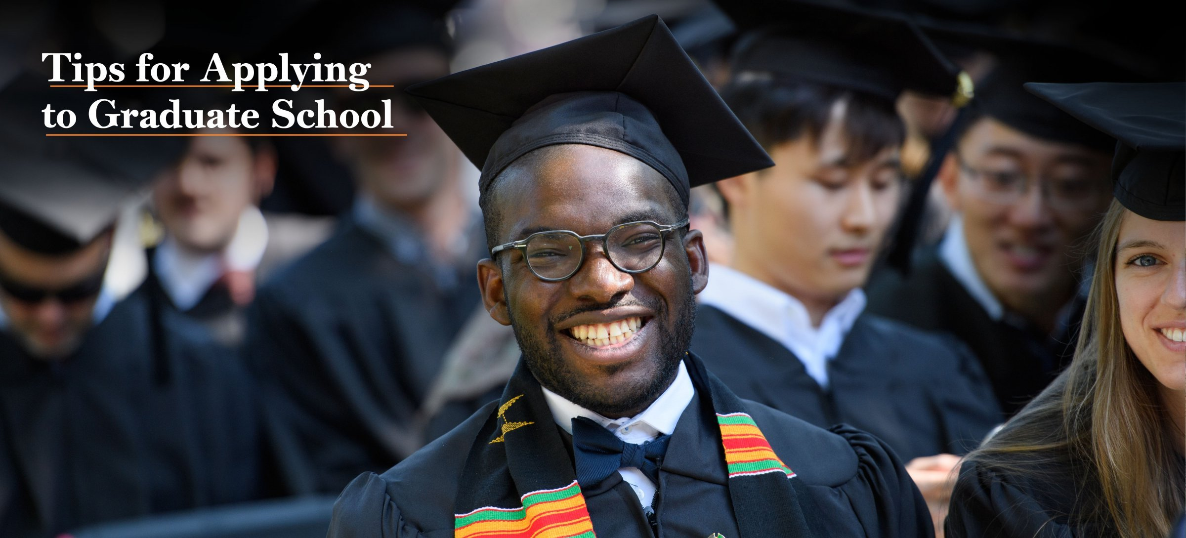 Arican American young man at his graduation smiling with a group of graduates